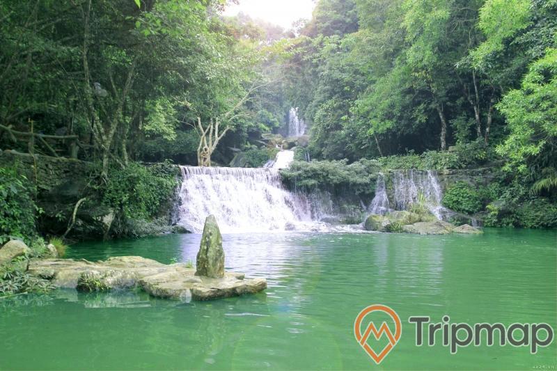 bể tắm tự nhiên khu du lịch Thác Đa, thác nước đang chảy xuống hồ, cây cối xanh tươi cạnh thác nước, bờ đá tự nhiên ở giữa hồ nước, ảnh chụp ngoài trời