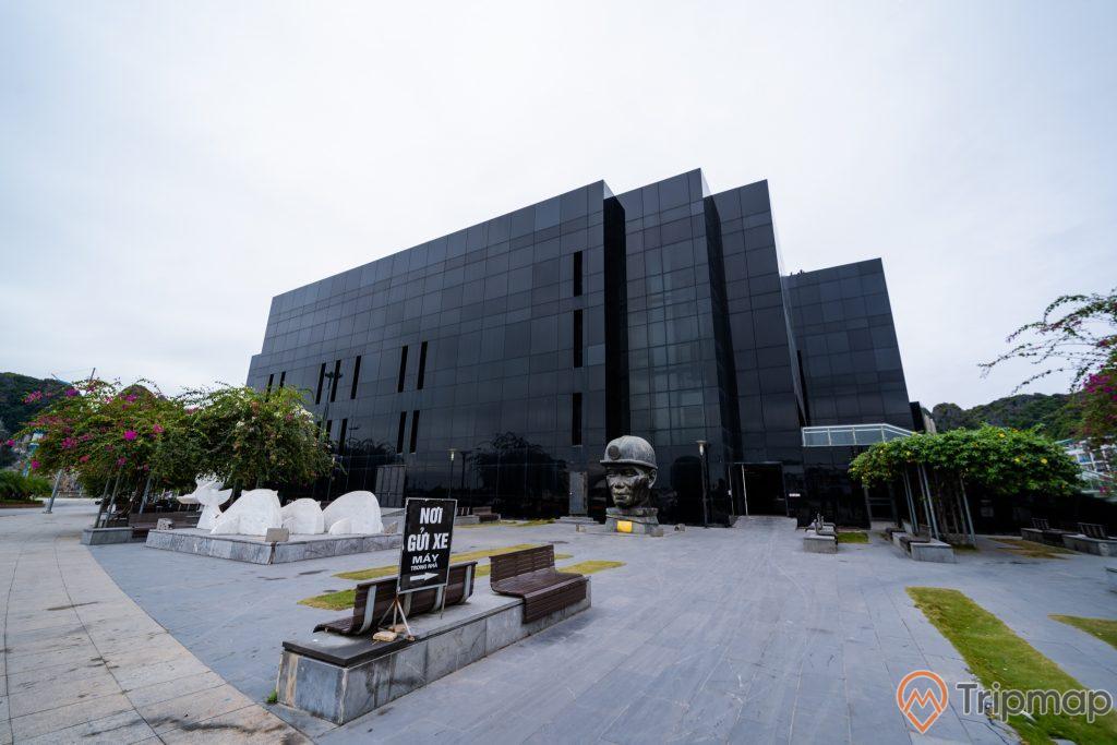 Bảo tàng Quảng Ninh, nhà kính màu đen, tượng người thợ mỏ, ghế đá, cây xanh, ảnh chụp ban ngày