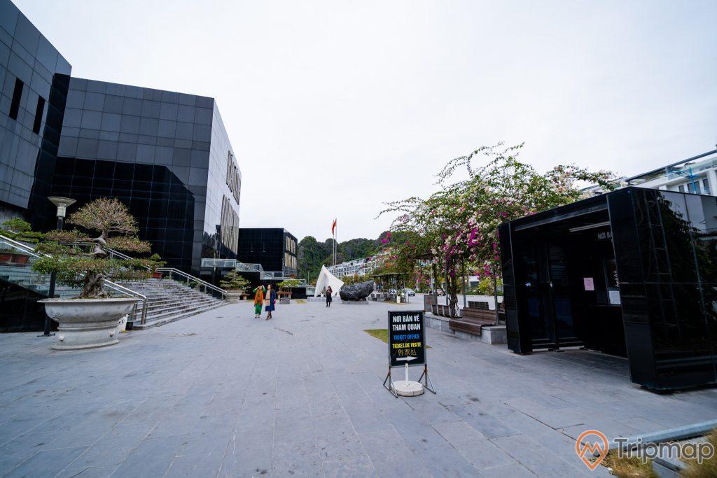 Bảo tàng Quảng Ninh, nền đất màu xám, chậu cây, bậc thang màu xám, người đang đi trên nền đất màu xám, cây hoa giấy, quầy bán vé, ảnh chụp ban ngày