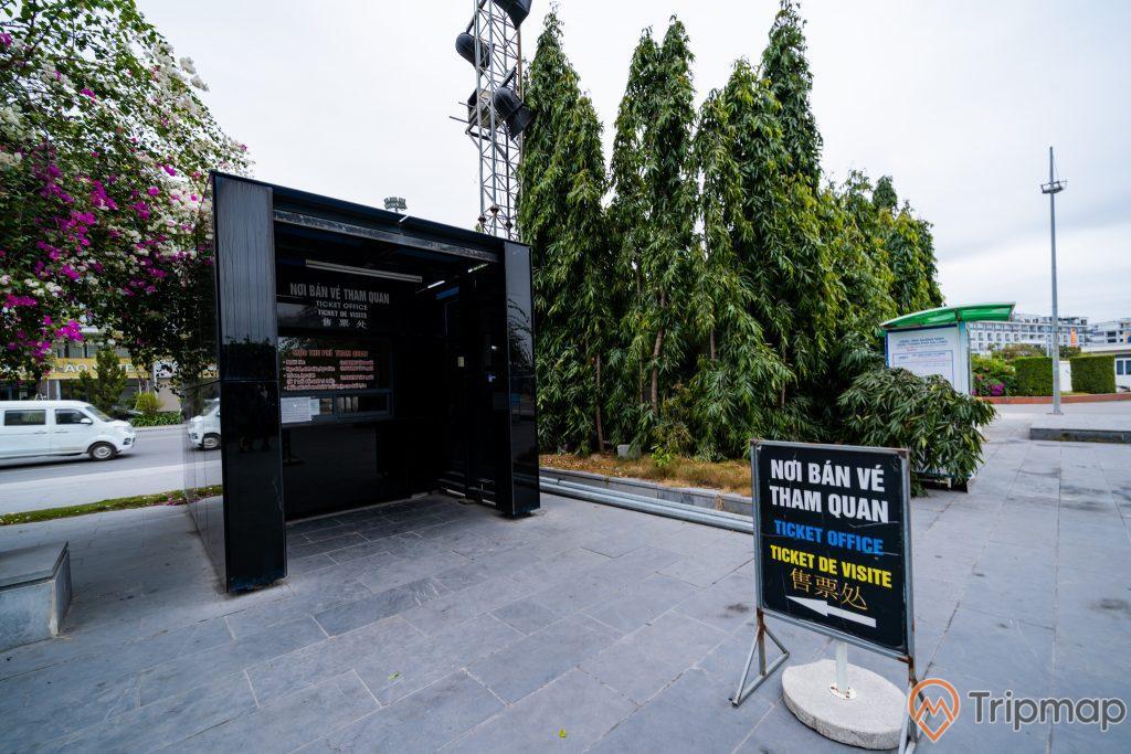 Bảo tàng Quảng Ninh, nền đường màu xám, bảng chỉ dẫn màu đen, nhiều cây xanh, ô tô màu trắng, cây hoa giấy, ảnh chụp ban ngày