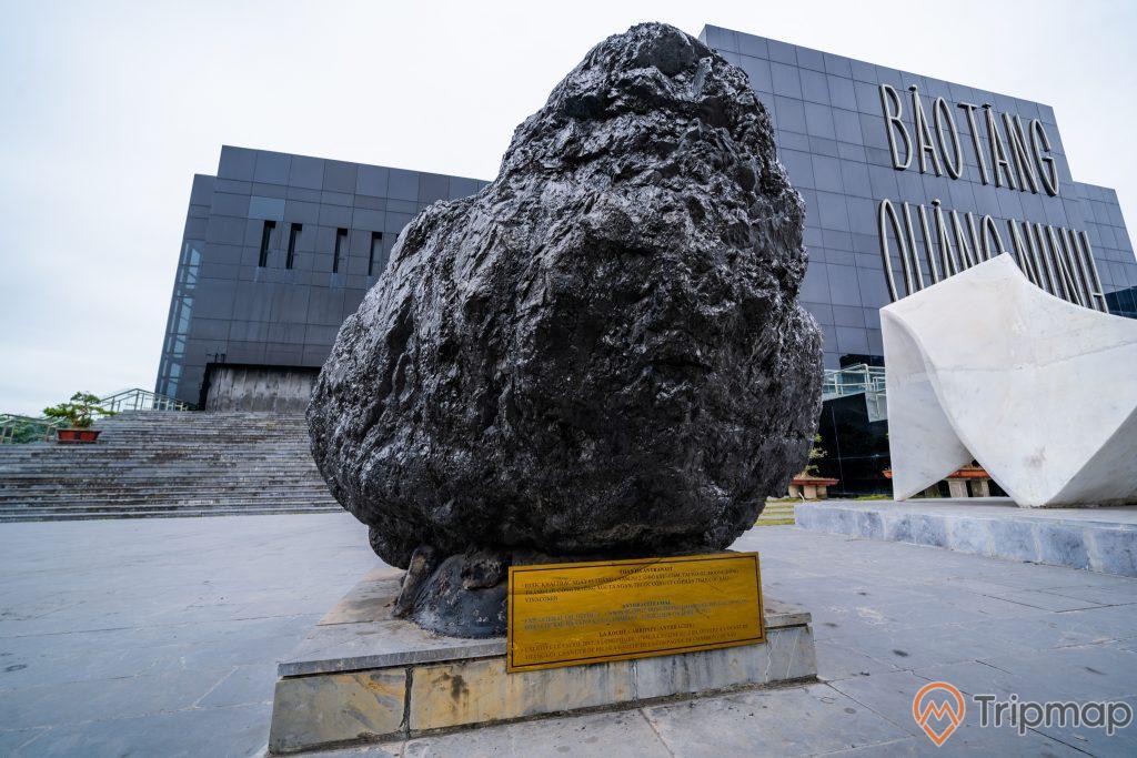 Bảo tàng Quảng Ninh, nền đường màu xám, bậc thang màu xám, tảng đá to màu đen, ảnh chụp ban ngày