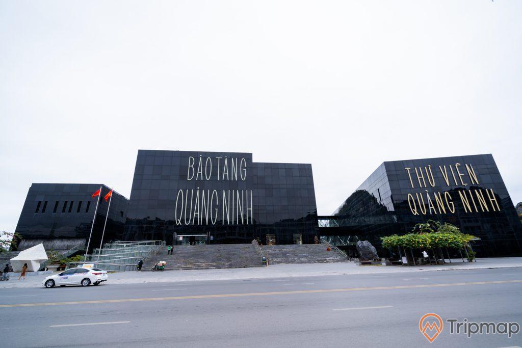 Bảo tàng Quảng Ninh, thư viện Quảng Ninh, nền đường màu xám, bậc thang màu xám, ô tô màu trắng, lá cờ màu đỏ, ảnh chụp ban ngày