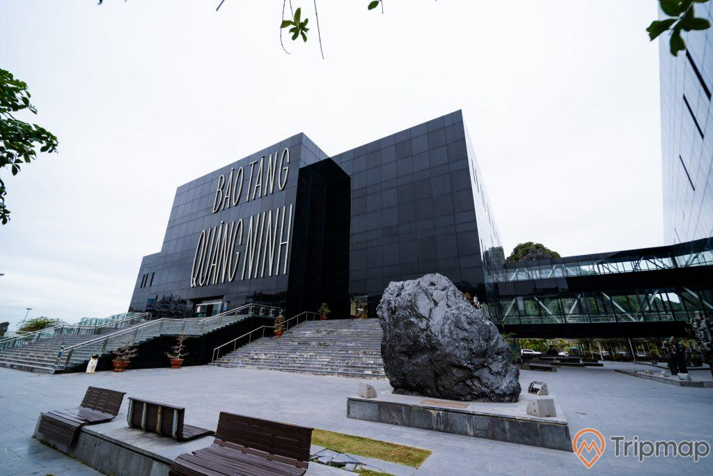 Bảo tàng Quảng Ninh, nền đường màu xám, bậc thang màu xám, nhiều chậu cây màu đỏ, nhiều ghế màu nâu, tảng đá to màu đen, nhà kính màu đen, ảnh chụp ban ngày