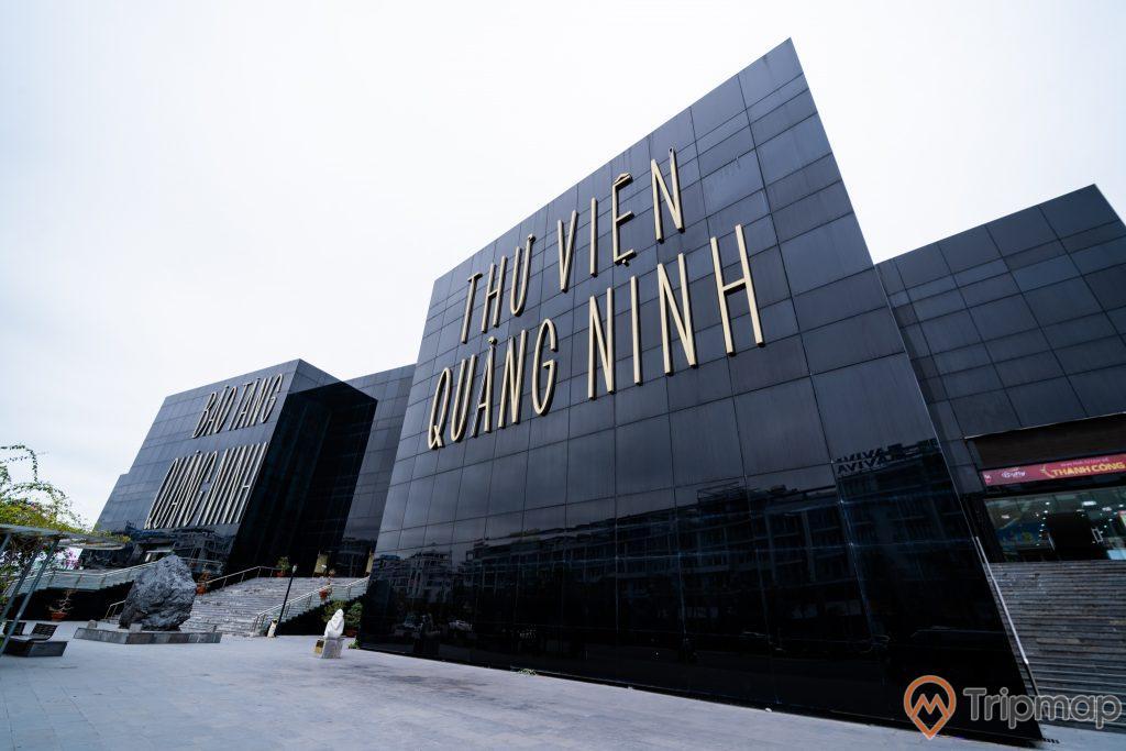 Thư Viện Quảng Ninh, nền đường màu xám, bậc thang màu xám, tảng đá to màu đen, nhà kính màu đen, ảnh chụp ban ngày