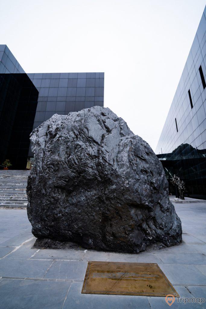 Bảo tàng Quảng Ninh, nền đường màu xám, tảng đá to màu đen, nhà kính màu đen, bậc thang màu xám, ảnh chụp ban ngày