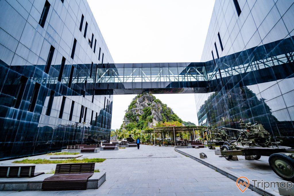 Bảo tàng Quảng Ninh, thư viện Quảng Ninh, hệ thống nhà cầu, nền đường màu xám, mô hình súng máy, ghế màu nâu, ngọn núi đá nhiều cây xanh phía xa, bãi cỏ xanh, ảnh chụp ban ngày