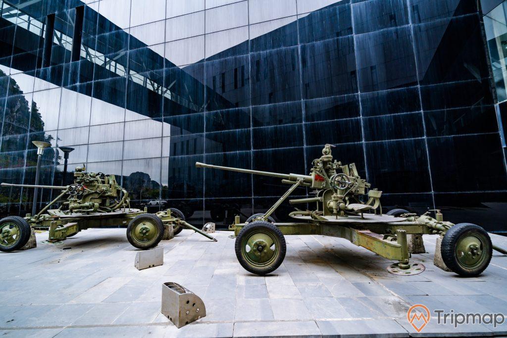 Bảo tàng Quảng Ninh, vũ khí quân sự sơn màu xanh, nền gạch màu xám, tòa nhà màu đen, ảnh chụp ban ngày