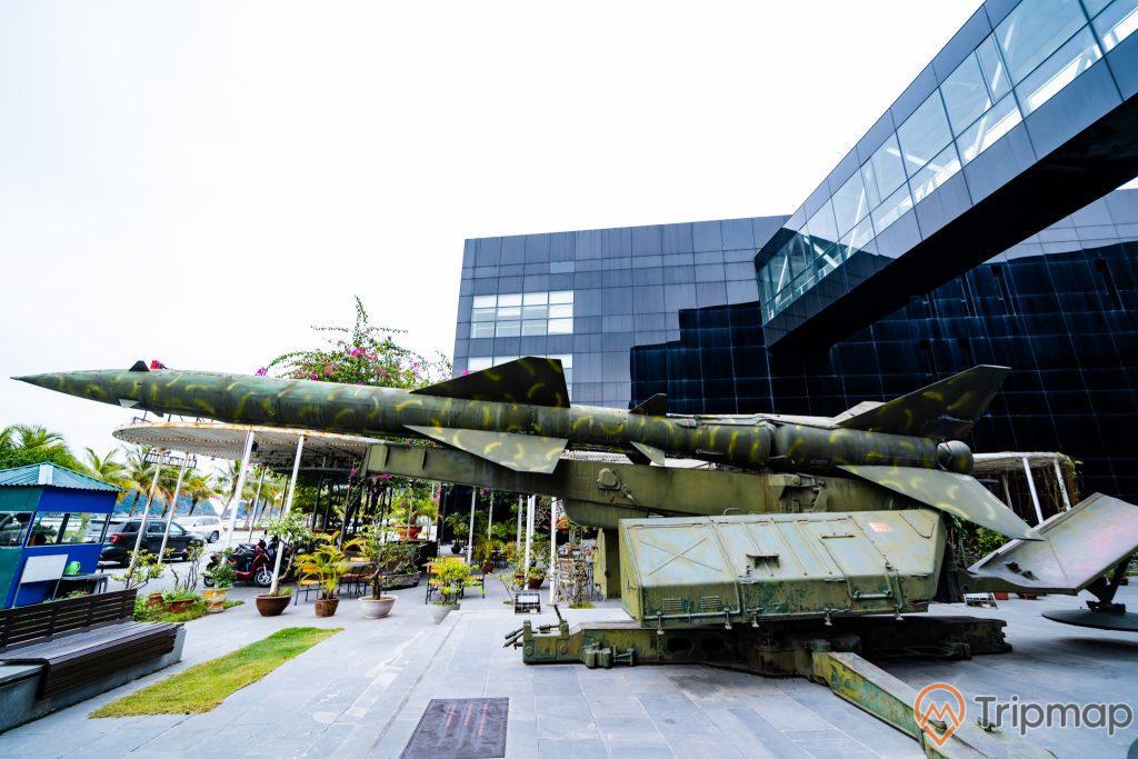 Bảo tàng Quảng Ninh, máy bay quân sự màu xanh, nền đường màu xám, bãi cỏ, nhiều chậu cây, ảnh chụp ban ngày, tòa nhà màu đen