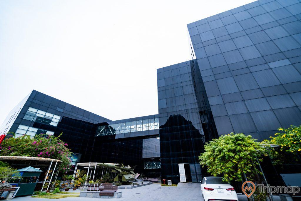 Bảo tàng Quảng Ninh, nền đường bằng gạch màu xám, ô tô màu trắng, nhiều cây xanh, cây hoa giấy, tòa nhà màu đen, ảnh chụp ban ngày