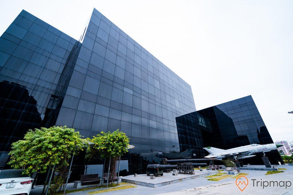 Bảo tàng Quảng Ninh, máy bay quân sự màu trắng, khẩu pháo màu đen, xe ô tô màu trắng, cây xanh, nền đường bằng gạch màu xám, tòa nhà màu đen, ảnh chụp ban ngày