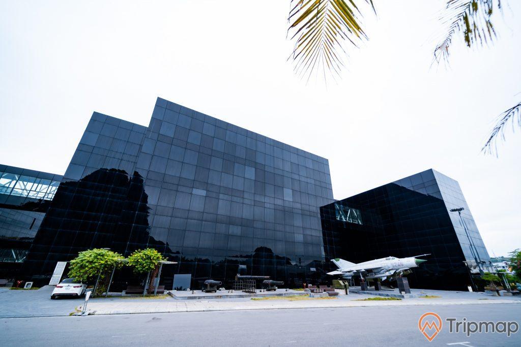Bảo tàng Quảng Ninh, nền đường màu xám, máy bay quân sự màu trắng, xe ô tô màu trắng, cây xanh, tòa nhà màu đen, ảnh chụp ban ngày