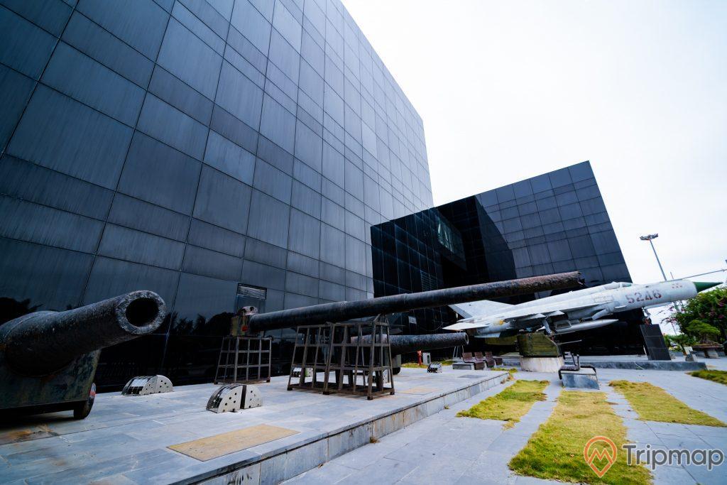 Bảo tàng Quảng Ninh, khẩu pháo màu đen, máy bay quân sự màu trắng, bãi cỏ xanh, nền đường bằng gạch màu xám, tòa nhà màu đen, ảnh chụp ban ngày