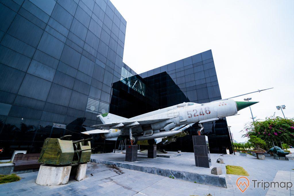 Bảo tàng Quảng Ninh, máy bay tiêm kích màu trắng, nền đường bằng gạch màu xám, tòa nhà màu đen, ảnh chụp ban ngày, cây hoa giấy