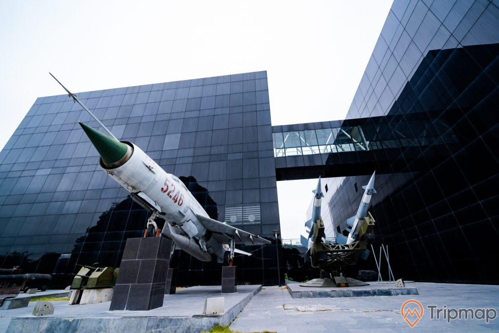 Bảo tàng Quảng Ninh, máy bay tiêm kích màu trắng, tên lừa màu xanh, nền đường bằng gạch màu xám, tòa nhà màu đen, ảnh chụp ban ngày