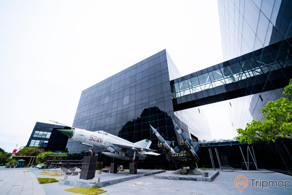 Bảo tàng Quảng Ninh, máy bay tiêm kích màu trắng, tên lửa màu xanh, nền đường bằng gạch màu xám, tòa nhà màu đen, nhà cầu, ảnh chụp ban ngày