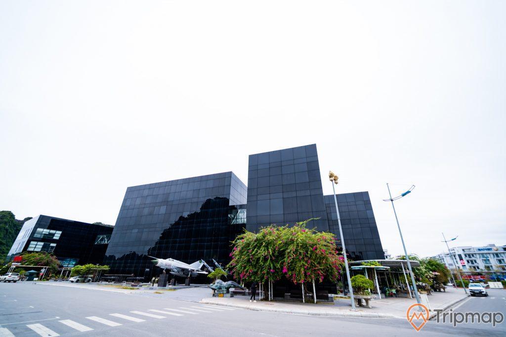 Bảo tàng Quảng Ninh, nền đường màu xám, máy bay tiêm kích màu trắng, cây hoa giấy, tòa nhà màu đen, ảnh chụp ban ngày