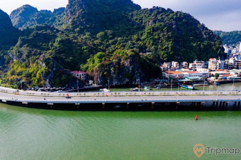 Cầu Bài Thơ, mặt nước biển màu xanh, ngọn núi nhiều cây xanh, nhiều nhà dân, ảnh chụp từ trên cao, ảnh chụp ban ngày, trời nắng