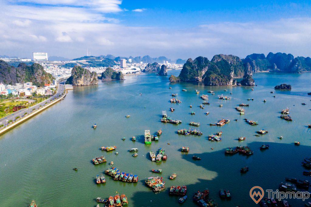 Cầu Bài Thơ, vịnh Hạ Long, nhiều thuyền đang đậu trên biển, mặt nước biển màu xanh, nhiều ngọn núi đá có cây xanh phía xa, trời xanh nhiều mây, ảnh chụp từ trên cao, ảnh chụp ban ngày, trời nắng