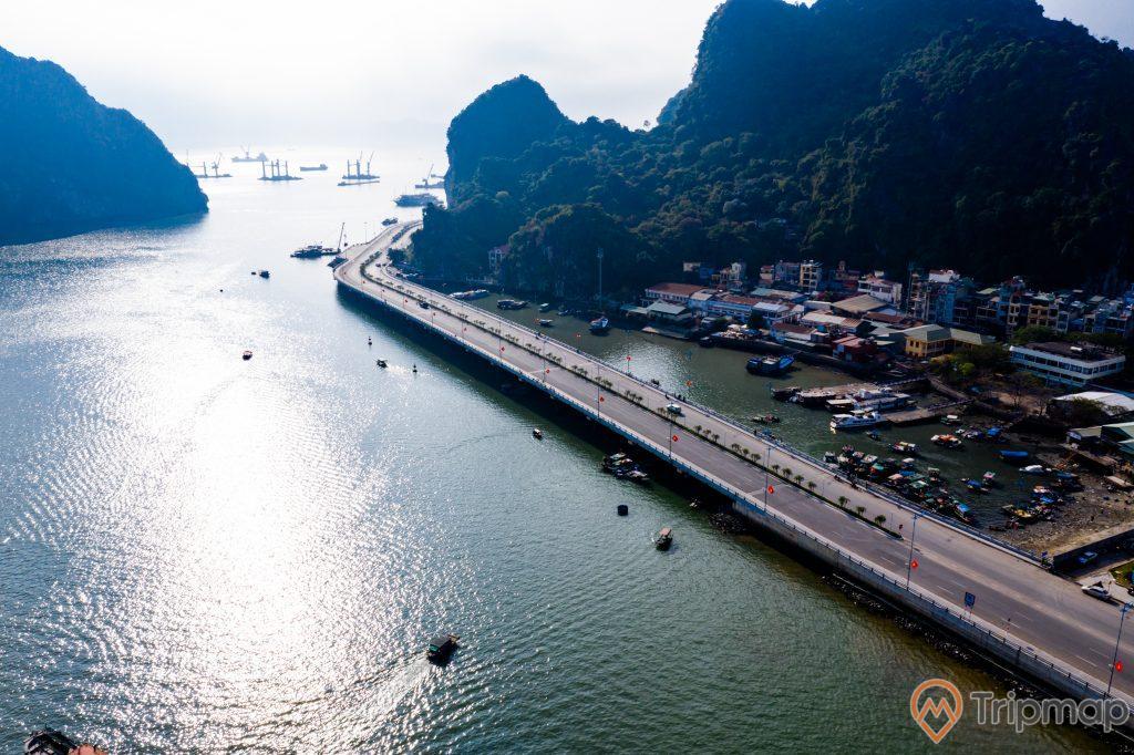 Cầu Bài Thơ, nhiều thuyền đang chạy trên biển, mặt nước biển màu xanh, con đường màu xám, nhiều nhà dân bên cạnh ngọn núi, nhiều ngọn núi đá có cây xanh, ảnh chụp từ trên cao, ảnh chụp ban ngày