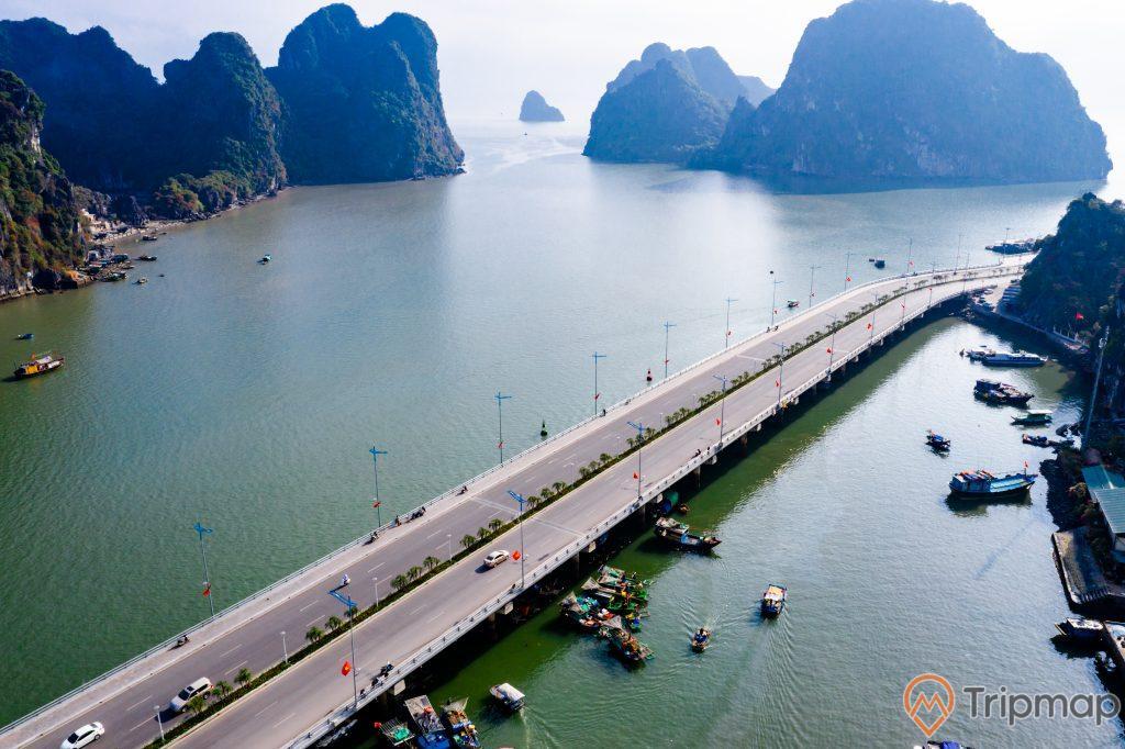 Cầu Bài Thơ, nhiều thuyền đang chạy trên biển, mặt nước biển màu xanh, con đường màu xám, nhiều ngọn núi đá có cây xanh, ảnh chụp từ trên cao, ảnh chụp ban ngày