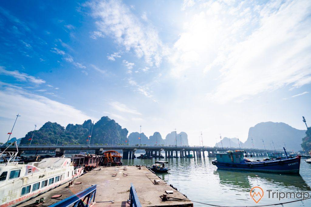 Cầu Bài Thơ, nhiều thuyền đang đỗ trên biển, mặt nước biển màu xanh, nhiều ngọn núi có cây xanh phía xa, trời xanh nhiều mây, ảnh chụp ban ngày