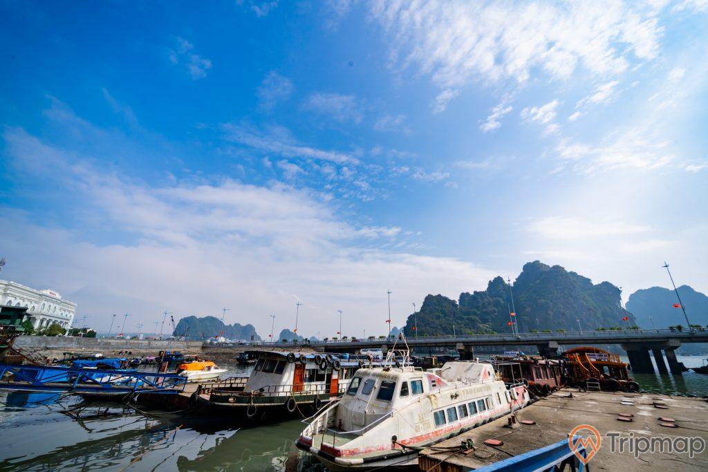 Cầu Bài Thơ, nhiều thuyền đang đỗ trên biển, nhiều ngọn núi có cây xanh phía xa, trời xanh nhiều mây, ảnh chụp ban ngày