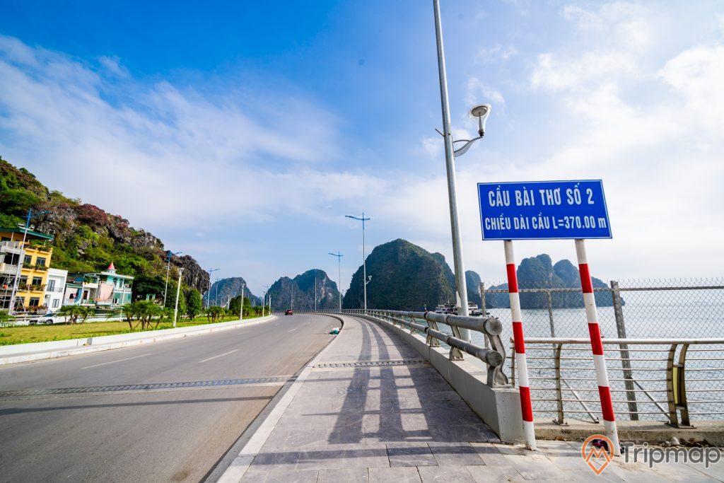Cầu Bài Thơ, con đường màu xám, bảng chỉ dẫn chữ trắng trên nền xanh, nhà dân bên cạnh ngọn núi có cây xanh, trời xanh nhiều mây, trời nắng, ảnh chụp ban ngày