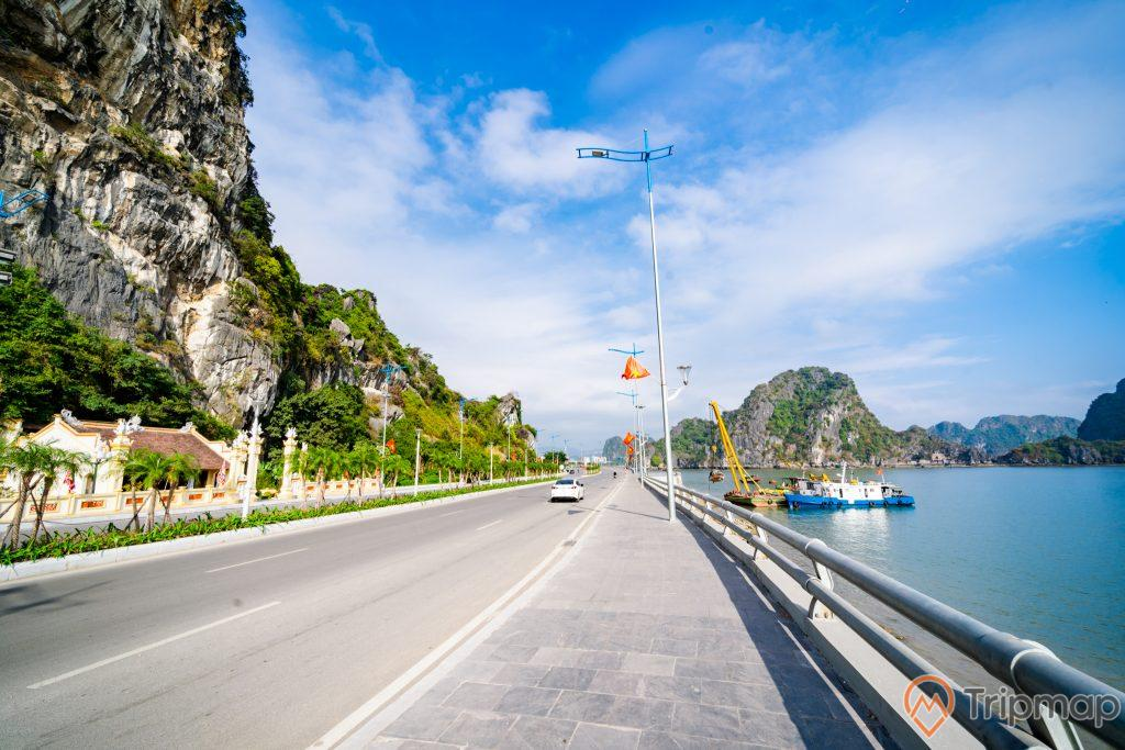 Cầu Bài Thơ, miếu Thổ Thần, ngọn núi đá to màu xám có cây xanh, con đường màu xám, vỉa hè bằng gạch màu xám, trời xanh nhiều mây, trời nắng, ảnh chụp ban ngày