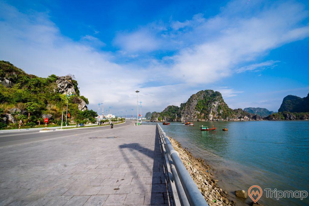 Cầu Bài Thơ, vỉa hè bằng gạch màu xám, nước biển màu xanh, nhiều thuyền đang chạy trên biển, nhiều ngọn núi đá có cây xanh phía xa, trời xanh nhiều mây, trời nắng, ảnh chụp ban ngày