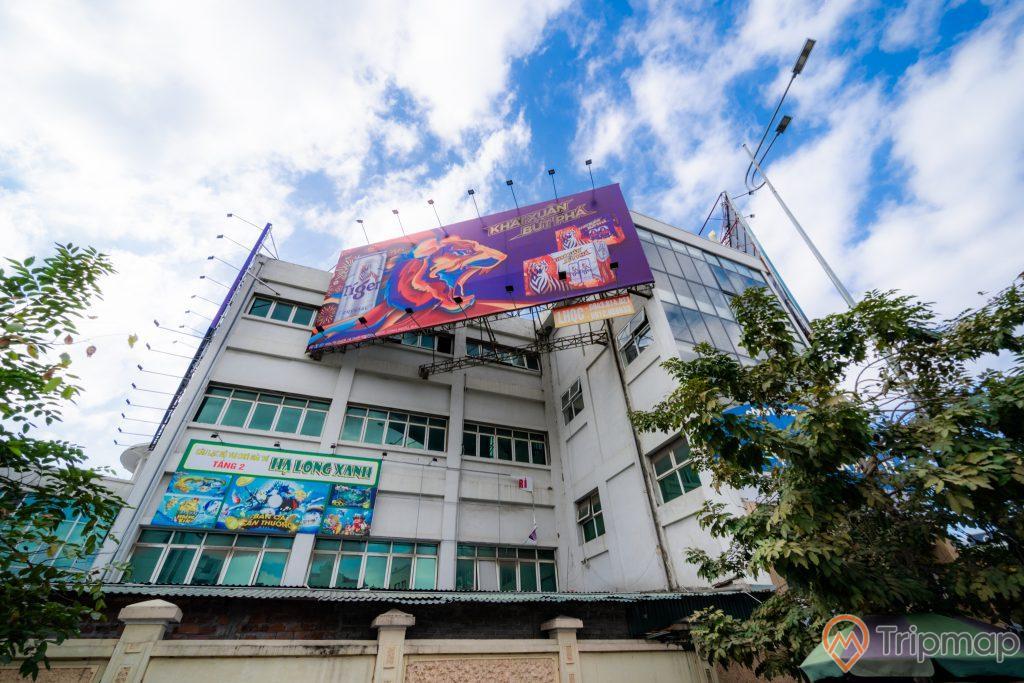 Chợ Hạ Long 2 , Chợ Loong Toòng, tòa nhà màu trắng, biển quảng cáo màu tím, nhiều cây xanh, cột đen, trời xanh nhiều mây, ảnh chụp ban ngày