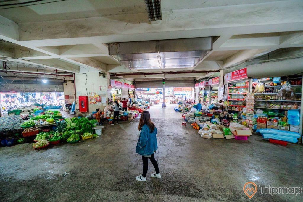 Chợ Hạ Long 2 , Chợ Loong Toòng, cô gái mặc áo xanh đang đứng trên nền đường màu xám, trần nhà màu trắng, ảnh chụp ban ngày