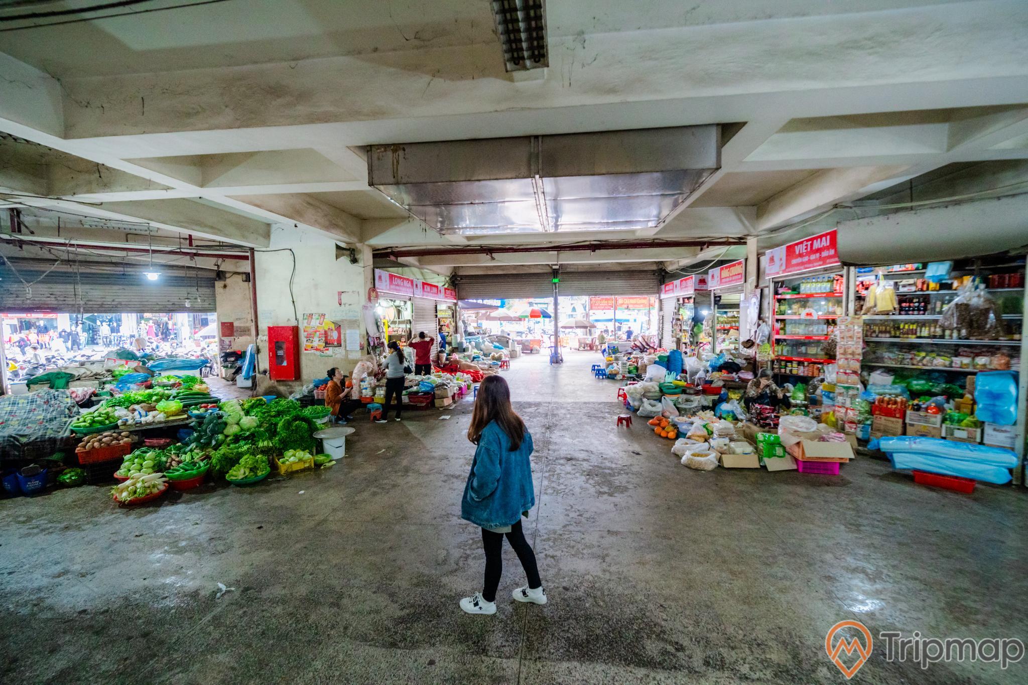 Chợ Hạ Long, Chợ Loong Toòng, cô gái mặc áo xanh đang đứng trên nền đường màu xám, trần nhà màu trắng, ảnh chụp ban ngày
