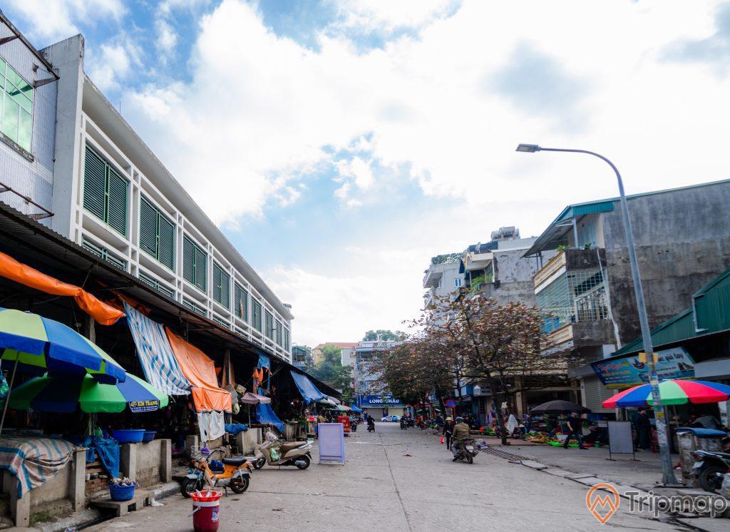 Chợ Hạ Long 2 , Chợ Loong Toòng, nền đường màu xám, cây cột đèn, nhiều nhà dân, trời xanh mấy trắng, nhiều xe máy trên nền đường màu xám, ảnh chụp ban ngày