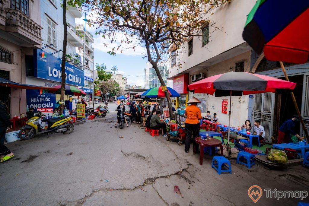 Chợ Hạ Long 2 , Chợ Loong Toòng, nền đường màu xám, nhiều người đang ngồi tại các quán ăn vỉa hè, xe máy màu vàng trên nền đường màu xám, người đàn bà đang đội nón, ảnh chụp ban ngày