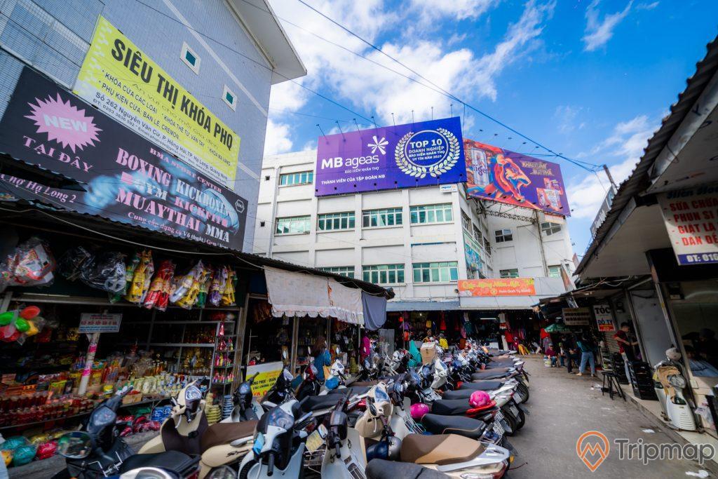Chợ Hạ Long 2 , Chợ Loong Toòng, nhiều xe máy đang đỗ trên nền đường màu xám, cửa hàng tạp hóa, biển quảng cáo màu vàng, biển quảng cáo màu xanh, nhà cao tầng có nhiều cửa sổ, trời xanh mây trắng, ảnh chụp ban ngày