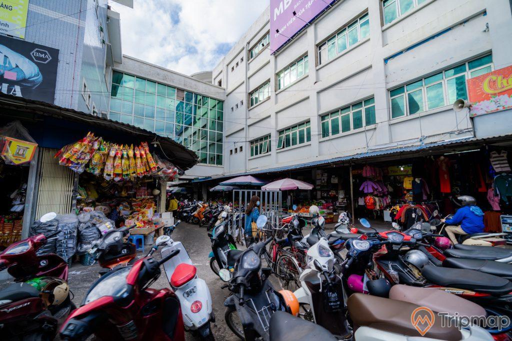 Chợ Hạ Long 2 , Chợ Loong Toòng, nhiều xe máy đang đỗ trên nền đường màu xám, tòa nhà nhiều cửa sổ, quán tạp hóa, trời nhiều mây, ảnh chụp ban ngày