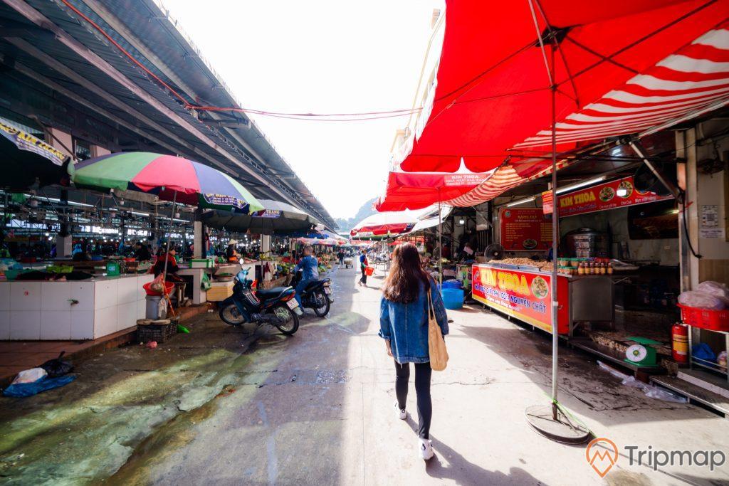 Chợ Hạ Long, Chợ Hòn Gai, cô gái mặc áo xanh đang đi trên nền đường màu xám, nhiều ô màu đỏ, nhiều xe máy, trời nắng, ảnh chụp ban ngày