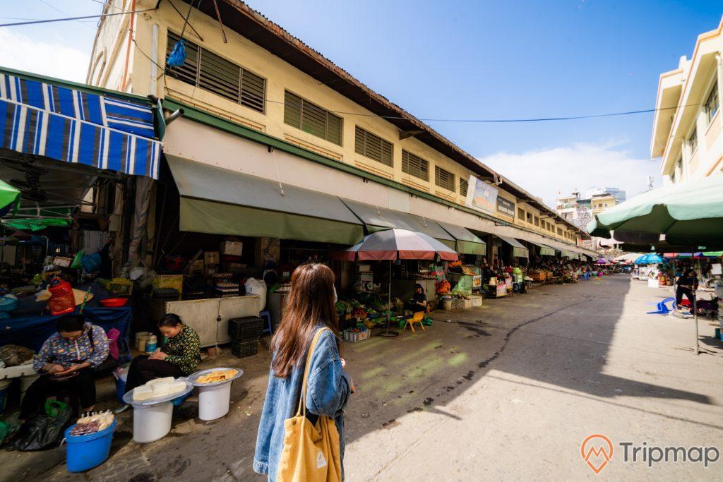 Chợ Hạ Long, chợ Hòn Gai, người phụ nữ mặc áo xanh đi bộ, nền đường màu xám, tòa nhà sơn màu vàng, trời xanh mây trắng, ảnh chụp ban ngày