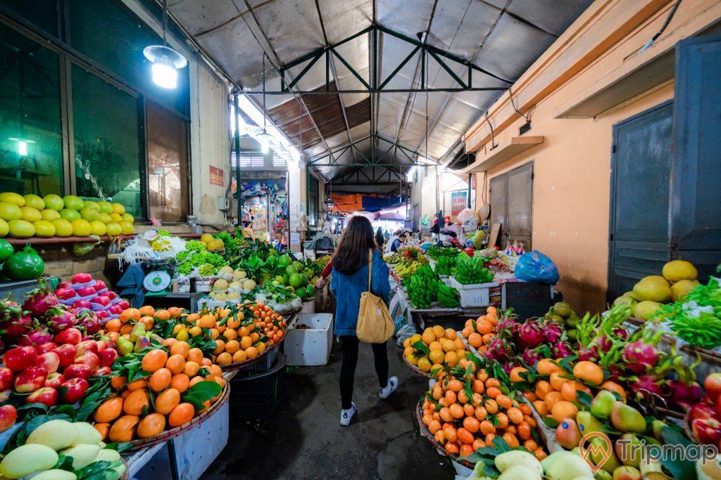 Chợ Hạ Long, chợ Hòn Gai, quầy bán hoa quả tại chợ, cô gái mặc áo xanh đang đi trên nền đất màu xám, rổ đựng cam, rổ đựng xoài, rổ đựng thanh long, rổ đựng táo, nhà sơn màu cam, ảnh chụp ban ngày