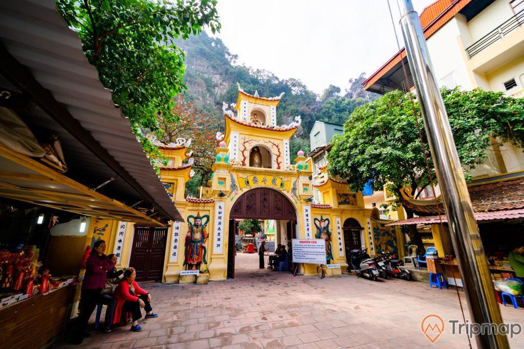 Chùa Long Tiên, nền gạch màu đỏ, người đang ngồi trên nền gạch, cây cột cờ, nhiều cây xanh, cổng chùa màu vàng nhiều chữ hán, ảnh chụp ban ngày