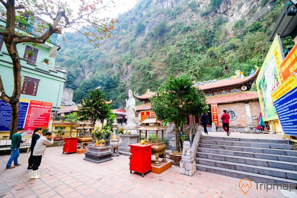 Chùa Long Tiên, nền gạch màu đỏ, 2 chậu cây, tượng phật màu trắng, người đang cầu nguyện, ngọn núi đá có cây xanh phía sau, bậc thang bằng đá màu xám, ảnh chụp ban ngày