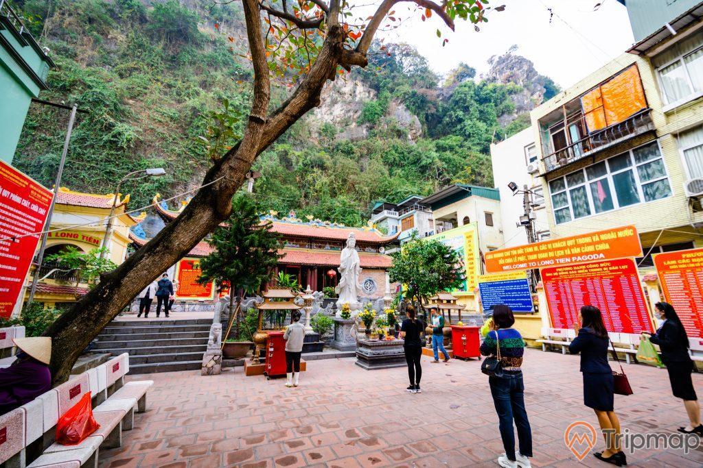Chùa Long Tiên, tượng Phật Quan Thế Âm Bồ Tát, nền gạch màu đỏ, nhiều người đang cầu nguyện, hàng ghế đá, bảng thông báo màu đỏ, bậc thang màu xám, nhà dân màu vàng, ngọn núi đá nhiều cây xanh, ảnh chụp ban ngày