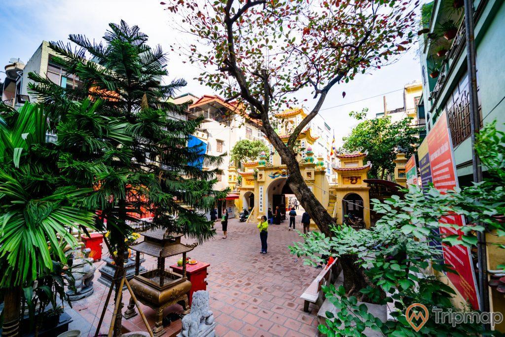 Chùa Long Tiên, nền gạch màu đỏ, nhiều cây xanh, nhiều người đang đi trên nền gạch màu đỏ, hàng ghế đá, tượng kỳ lân bằng đá, ảnh chụp ban ngày