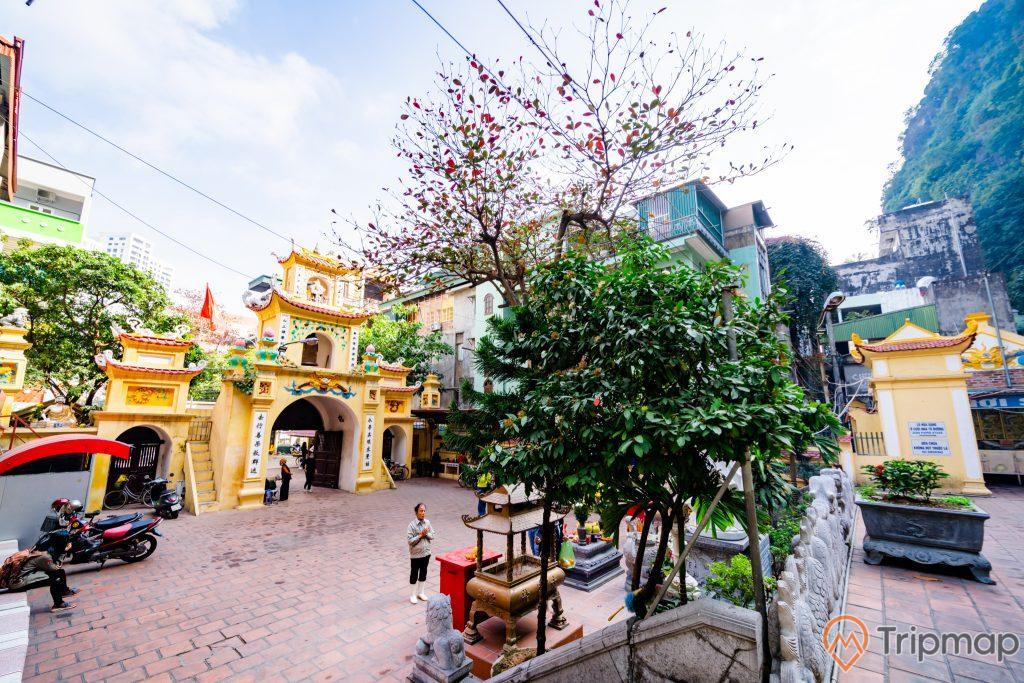 chùa Long Tiên, nền gạch màu đỏ, nhiều xe máy, nhiều cây xanh, cổng chùa sơn màu vàng, tượng kỳ lân bằng đá, ảnh chụp ban ngày