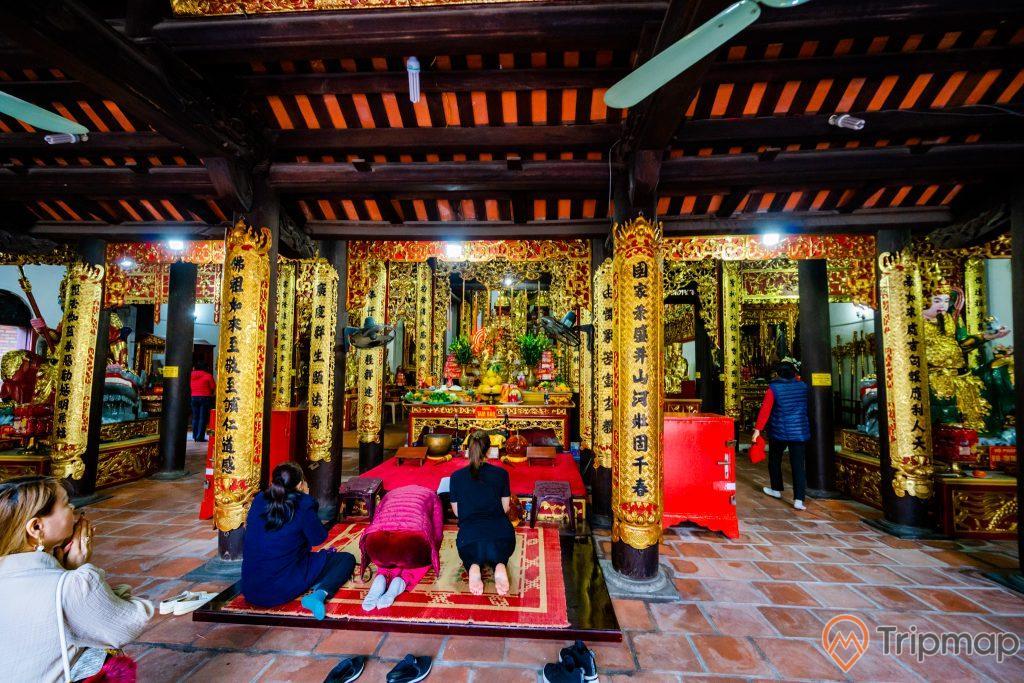 Chùa Long Tiên, nền gạch màu đỏ, nhiều người đang cầu nguyện, cây cột nhà có hoa văn màu vàng nhiều chữ hán, trần nhà bằng gỗ màu nâu, ảnh chụp ban ngày