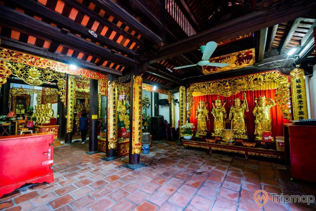 Chùa Long Tiên, nền gạch màu đỏ, tượng các tướng lĩnh nhà Trần, cây quạt trần, trần nhà bằng gỗ màu nâu, nhiều cây cột nhà có hoa văn màu vàng nhiều chữ hán, ảnh chụp ban ngày