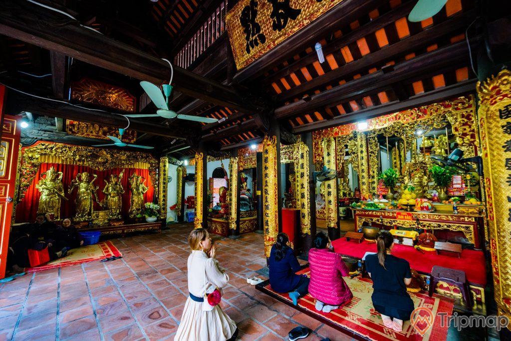 Chùa Long Tiền, nền gạch màu đỏ, nhiều người đang cầu nguyện, tượng các tướng lĩnh nhà Trần, nhiều quạt trần, trần nhà bằng gỗ màu nâu, nhiều cây cột nhà có hoa văn màu vàng có chữ hán, ảnh chụp ban ngày