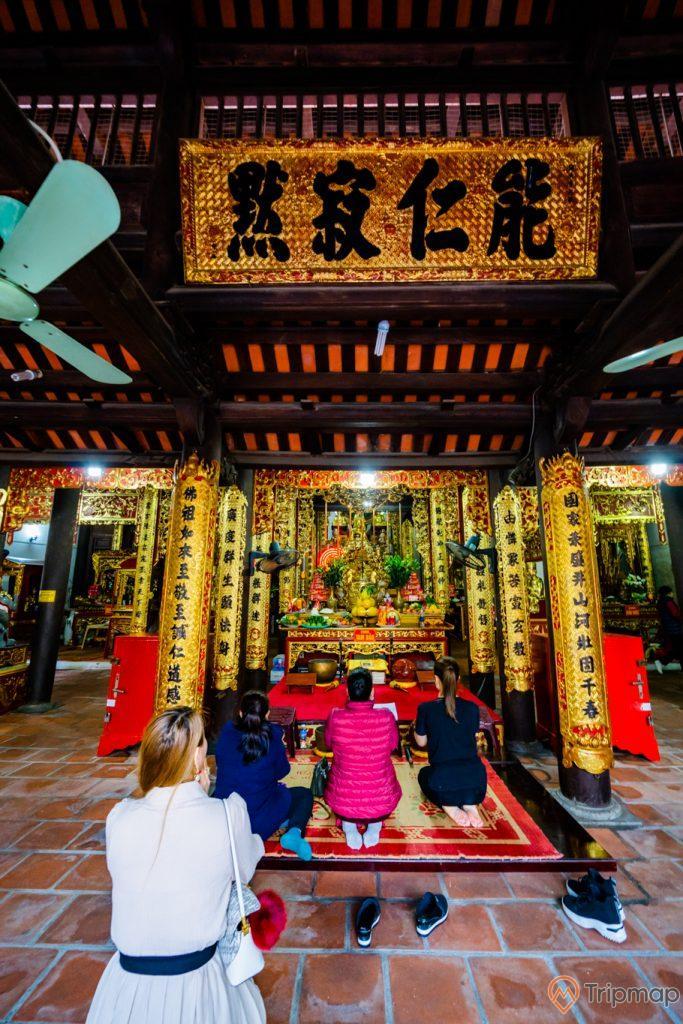 Chùa Long Tiên, nền gạch màu đỏ, nhiều người đang cầu nguyện, tượng Đức thánh Trần Hưng Đạo, nhiều cây cột nhà màu vàng có hoa văn nhiều chữ hán, cây quạt trần, trần nhà bằng gỗ màu nâu, ảnh chụp ban ngày