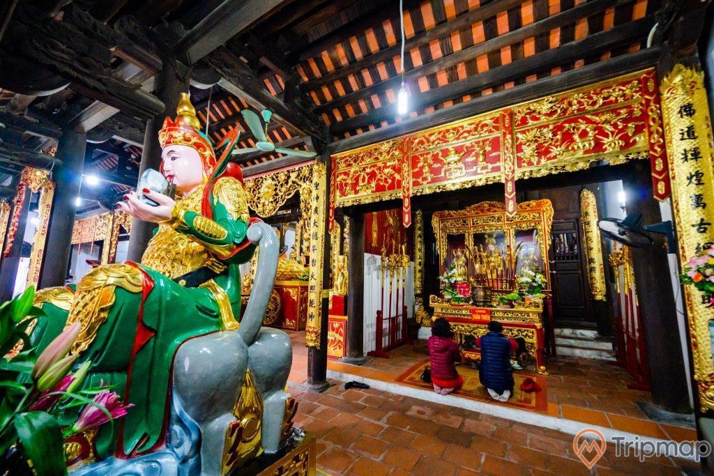 Chùa Long Tiên, tượng hộ pháp, nền gạch màu đỏ, người đang cầu nguyện, gian thờ có hoa văn màu vàng, trần nhà bằng gỗ màu nâu
