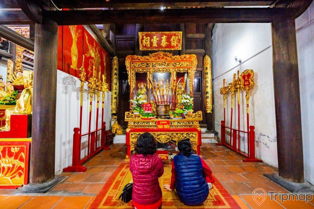 Chùa Long Tiên, Cung Trần Triều, nền gạch màu đỏ, người đang cầu nguyện, cây cột nhà màu nâu, hoa văn màu vàng có chữ hán
